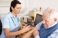 British nurse giving injection to senior man Stock Images