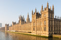 British parliament beautifully lit by the early morning sun at dawn the westminster at full glory on the side of river thames in Royalty Free Stock Photography