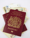 British passports and cash on white background Stock Photos