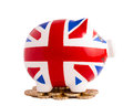 British piggy bank smiling union jack standing on pound coins on white background Royalty Free Stock Photography