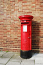British postbox red and vintage on the sidewalk next to a brick wall building united kingdom Royalty Free Stock Photo