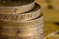 British pound coins spelling amen stacked and showing with christian cross symbols Stock Images