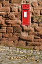 British red mail box mounted into stone wall. Royalty Free Stock Photo