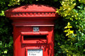 British red post box traditional with garden hedge in the background Royalty Free Stock Photography