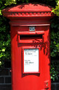 British red post box traditional with garden hedge in the background Stock Photography