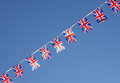 British union jack flag bunting row flags against blue sky Stock Photos