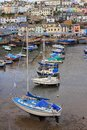 BRIXHAM, DEVON, UK, NOV 02 2015: Small boats moored at low tide in the fishing port, with the town of Brixham in the background Royalty Free Stock Photo
