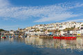 Brixham harbour devon with houses on the hillside and colourful boats moored a still summer calm summer day blue sky a Royalty Free Stock Image