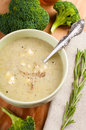 Broccoli cream soup with a sprig of rosemary in ceramic bowl napkin and spoon on wooden table Stock Images