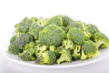 Broccoli florets on a white plate fresh cut raw and background Royalty Free Stock Image