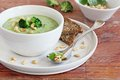 Broccoli potato soup with pine nuts and broccoli topping selective focus Royalty Free Stock Images