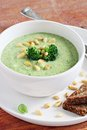 Broccoli potato soup with pine nuts and broccoli topping selective focus Royalty Free Stock Photos