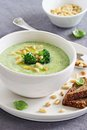 Broccoli potato soup with pine nuts and broccoli topping selective focus Stock Photos