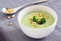 Broccoli potato soup with pine nuts and broccoli topping selective focus Royalty Free Stock Photo