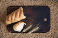 Broken bread and ears on a kitchen board against a background of wheat grains Royalty Free Stock Photo