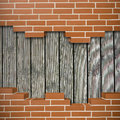 Broken brickwall background red with old wooden planks in the Royalty Free Stock Photo