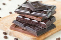 Broken chocolate bars of different kinds of chocolate are stacked on a wooden board, around bit of coffee beans