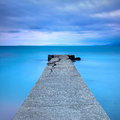 Broken concrete pier or jetty and rocks on a blue sea hills on background long exposure photography Royalty Free Stock Image