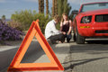 Broken down car with red warning triangle emergency stop sign in foreground blurred couple sitting by Stock Photos