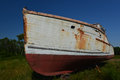 A broken down hulk of a lobster boat rusting and in need repairs large fishing sits in an open farm field waiting for new owners Royalty Free Stock Photography
