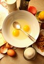 Broken eggs in a dish and the ingredients for the recipe Stock Image