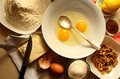 Broken eggs in a dish and the ingredients for the recipe Stock Photo