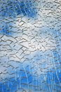 Broken glass texture, blue sky clouds seen thgough it Royalty Free Stock Photo