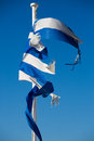A broken greek flag with a clear blue sky waving the wind in the background this images is reflection of the country Stock Image
