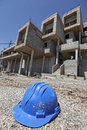 Broken hard hat and unfinished apartments in background crisis in development industry Royalty Free Stock Image