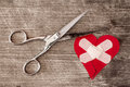 Broken heart with bandage and scissors Royalty Free Stock Photo