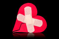 Broken heart fixed with adhesive bandage plaster isolated on black background Stock Photography