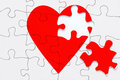 Broken heart jigsaw a red puzzle with a piece on the side good image for a love romance and valentine themes Royalty Free Stock Image