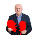 Broken heart old man closeup portrait senior executive business corporate employee mature guy holding in his hands about to Stock Image