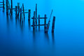 Broken jetty on calm waters long exposure Stock Image