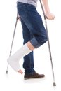 Broken leg man standing with crutches with bandage on on white isolated Stock Photos