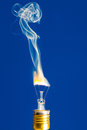 Broken light bulb burn out with flame on blue Royalty Free Stock Photo