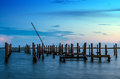 Broken pier and mast of broken ship in water after sunset Royalty Free Stock Photo