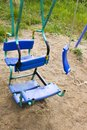 Broken plastic children`s swing in a playground, painted, welding on metal, so as not to break, old and unsafe swings