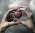 Broken red heart in hands on stormy sky Royalty Free Stock Photo