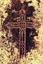 Broken and rusty iron rustic crucifix on old mossy tombstone. Abandoned symbol of religion. Royalty Free Stock Photo