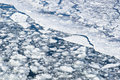 Broken slush ice floats down the river white icy surface and dark blue water in day time winter season Stock Images