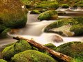 Broken trunk blocked between boulders at stream bank above bright blurred waves. Big mossy stones in clear water of river. Royalty Free Stock Photo