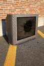 Broken tv old and television set abandoned on street and next to brick wall Stock Photo