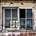 Broken window on old derelict abandoned building with missing glass pane and rotted wood frame with vintage peeling paint in Royalty Free Stock Images