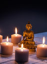 Bronze Buddha with warm lighted candles for concept of mindfulness Royalty Free Stock Photo