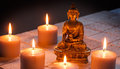 Bronze Buddha with warm lighted candles over limestone background Royalty Free Stock Photo