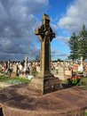 Bronze cross in cemetery elaborately decorated Royalty Free Stock Images