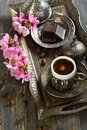 Bronze set for turkish coffee and blossoming branch on the old table Stock Photos