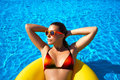 Bronzed beauty brunette sunbathing lying on a yellow big float suntan summertime colors Royalty Free Stock Images