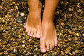Bronzed feet on stones Royalty Free Stock Image